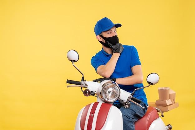 Jovem mensageiro masculino de uniforme azul no fundo amarelo trabalho covid- trabalho pandemia entrega serviço bicicleta de vírus