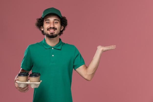 Jovem mensageiro masculino de uniforme verde e capa segurando xícaras de café marrom no fundo rosa entrega uniforme de serviço