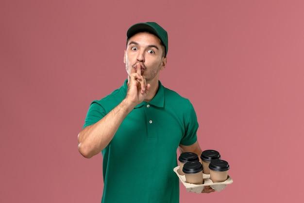 Jovem mensageiro masculino de uniforme verde segurando xícaras de café e pedindo para ficar em silêncio na mesa rosa
