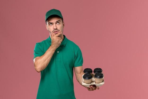 Jovem mensageiro masculino de uniforme verde segurando xícaras de café marrons pensando na mesa rosa claro de frente