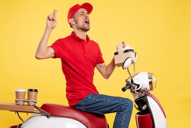 Jovem mensageiro masculino de uniforme vermelho com café em fundo amarelo