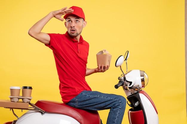 Jovem mensageiro masculino de uniforme vermelho com entrega de comida em fundo amarelo de frente