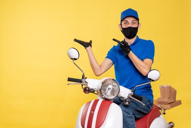 Jovem mensageiro masculino de vista frontal com uniforme azul e máscara em fundo amarelo