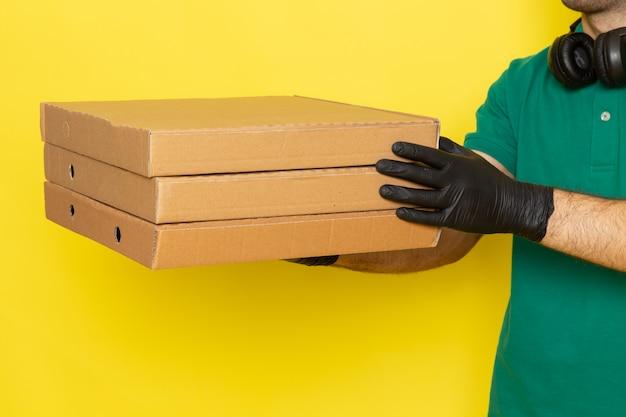 Jovem mensageiro masculino segurando caixas de entrega em amarelo