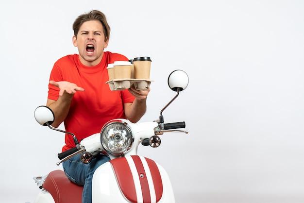 Jovem mensageiro nervoso, de uniforme vermelho, sentado na scooter e segurando pedidos na parede amarela