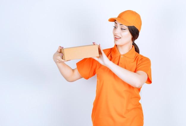 Jovem mensageiro segurando uma caixa de entrega no ar