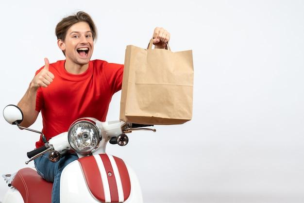 Jovem mensageiro sorridente com uniforme vermelho sentado na scooter segurando um saco de papel e fazendo um gesto de ok na parede amarela