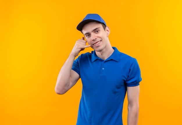 Jovem mensageiro vestindo uniforme azul e boné azul feliz me ligando com a mão