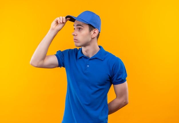 Jovem mensageiro vestindo uniforme azul e boné azul parece além de confuso