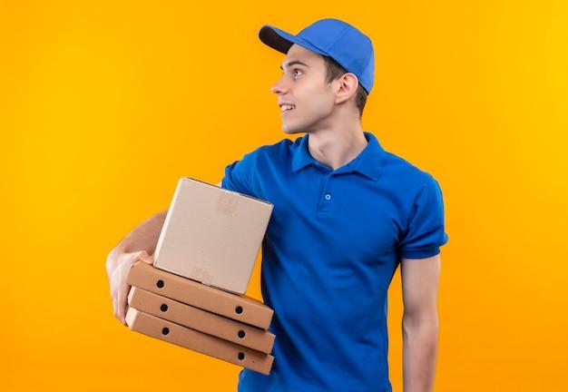 Jovem mensageiro vestindo uniforme azul e boné azul, parecendo além de segurar caixas