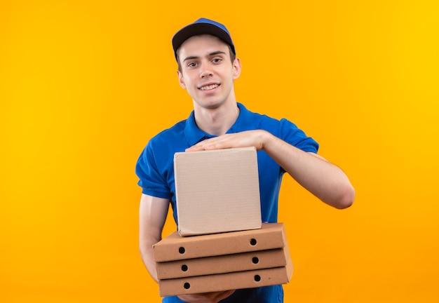 Jovem mensageiro vestindo uniforme azul e boné azul segurando caixas