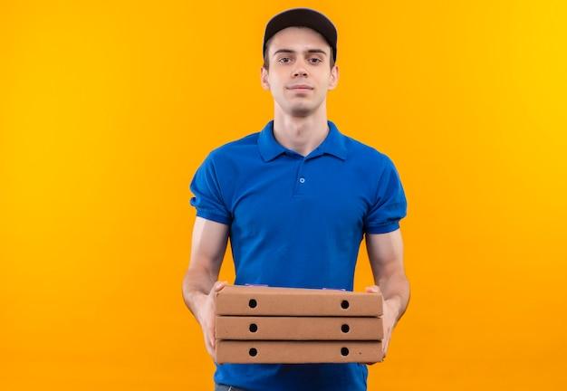 Jovem mensageiro vestindo uniforme azul e boné azul sorrindo segurando caixas