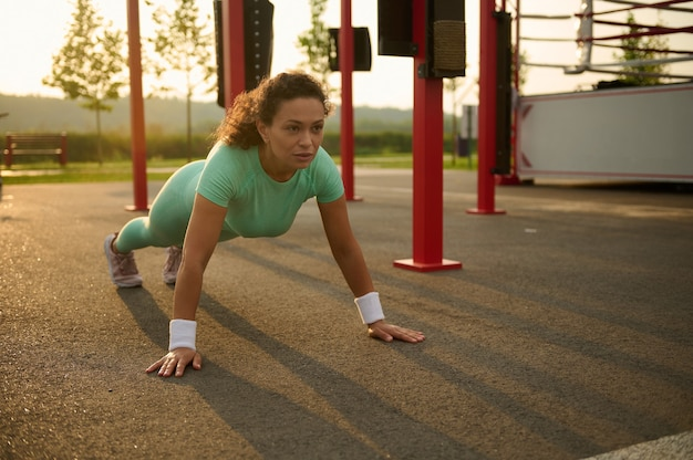 Jovem mestiça, atleta de mulher afro-americana malhando ao ar livre, fazendo flexões no campo de esportes no verão. estilo de vida ativo e saudável e conceito de fitness