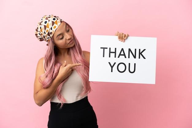 Jovem mestiça com cabelo rosa isolada em um fundo rosa segurando um cartaz com o texto obrigado e apontando-o