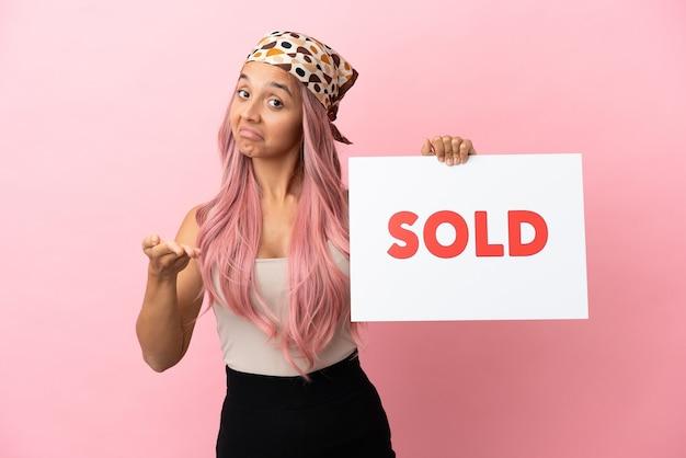 Jovem mestiça com cabelo rosa isolada em um fundo rosa segurando um cartaz com o texto vendido fazendo um acordo