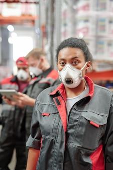 Jovem mestiça com roupa de trabalho e respirador protetor em pé durante o trabalho em um grande armazém contemporâneo