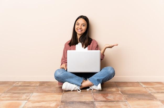 Jovem mestiça com um laptop sentada no chão, segurando o imaginário de copyspace na palma da mão para inserir um anúncio