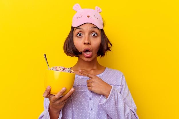 Jovem mestiça comendo cereais usando um pijama isolado na parede amarela apontando para o lado