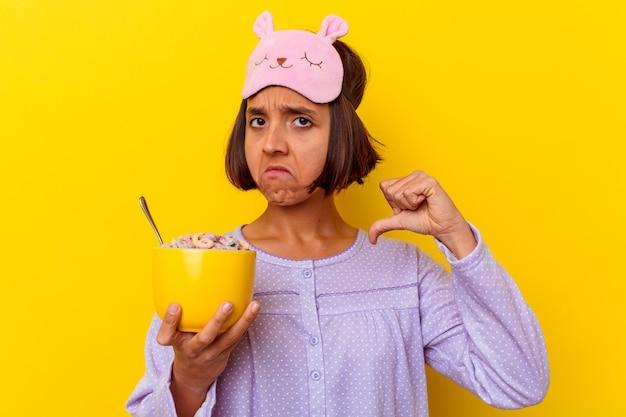 Jovem mestiça comendo cereais vestindo um pijama isolado na parede amarela sente-se orgulhosa e autoconfiante, exemplo a seguir.