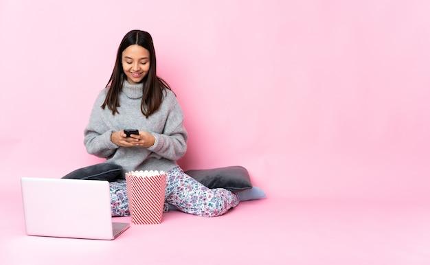 Jovem mestiça comendo pipoca enquanto assiste a um filme no laptop enviando uma mensagem no celular