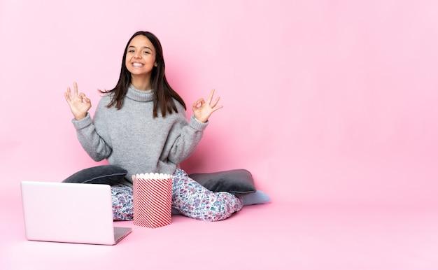 Jovem mestiça comendo pipoca enquanto assiste a um filme no laptop mostrando sinal de ok com as duas mãos