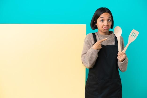 Jovem mestiça cozinheira com um grande cartaz isolado em um fundo azul apontando para as laterais com dúvidas