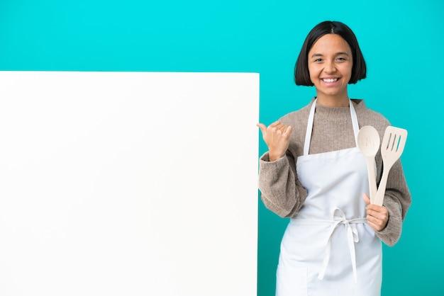 Jovem mestiça cozinheira com um grande cartaz isolado em um fundo azul apontando para o lado para apresentar um produto
