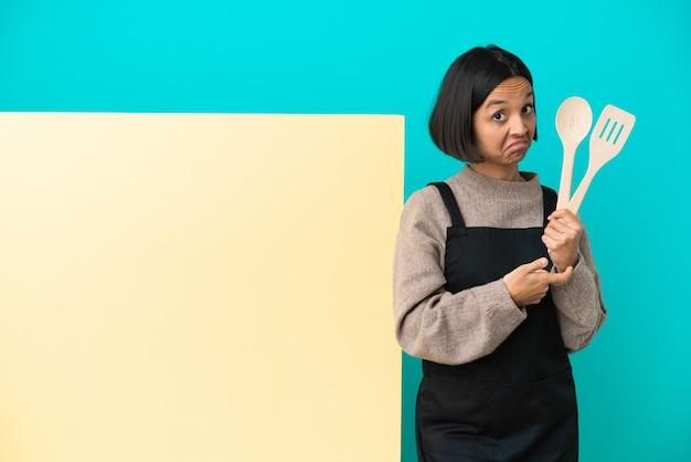 Jovem mestiça cozinheira com um grande cartaz isolado em um fundo azul fazendo o gesto de estar atrasado