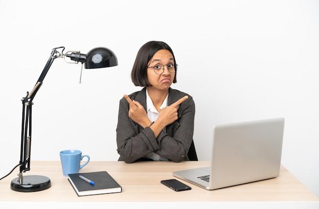 Jovem mestiça de negócios trabalhando em escritório apontando para as laterais com dúvidas