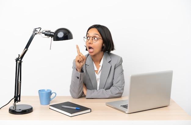 Jovem mestiça de negócios trabalhando em um escritório pensando em uma ideia apontando o dedo para cima