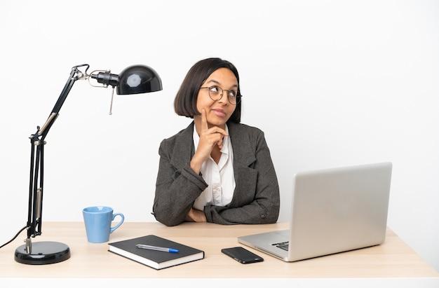Jovem mestiça de negócios trabalhando em um escritório pensando em uma ideia enquanto olha para cima
