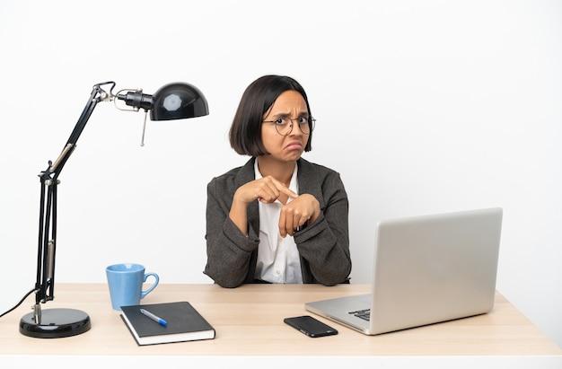 Jovem mestiça de negócios trabalhando no escritório fazendo o gesto de se atrasar