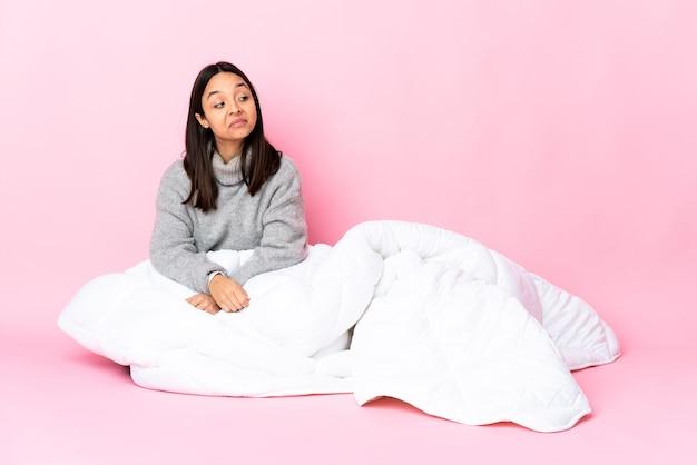 Jovem mestiça de pijama sentada no chão, com dúvidas enquanto olha de lado
