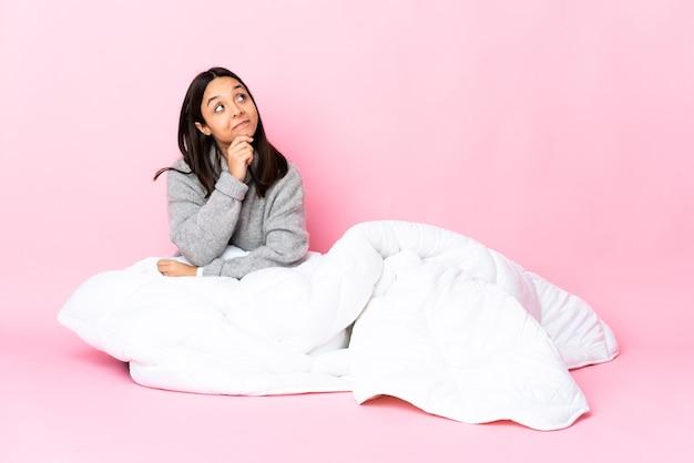 Jovem mestiça de pijama sentada no chão olhando para cima