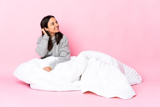 Jovem mestiça de pijama sentada no chão pensando em uma ideia