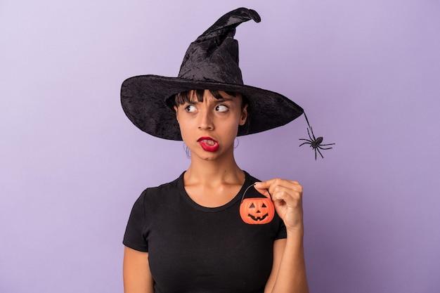 Jovem mestiça disfarçada de bruxa isolada em fundo roxo confusa, sente-se duvidosa e insegura.