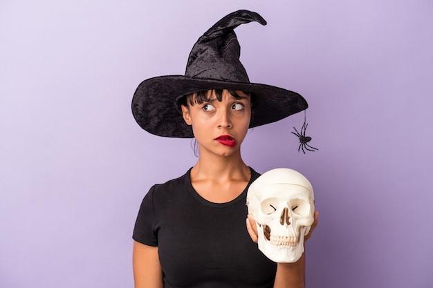 Jovem mestiça disfarçada de bruxa segurando uma caveira isolada em um fundo roxo confusa, sente-se em dúvida e insegura.