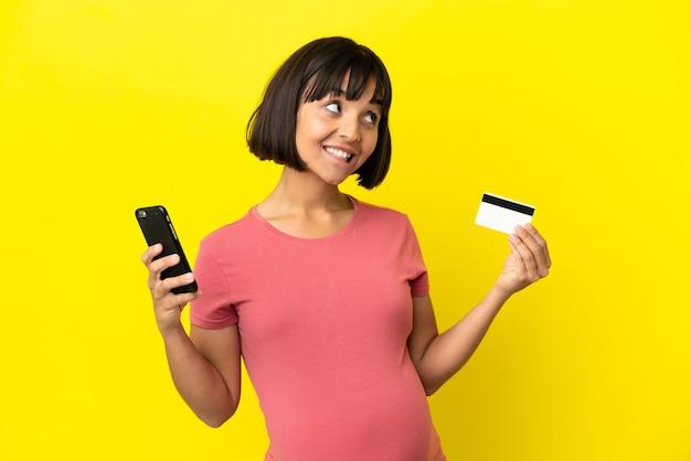 Jovem mestiça grávida isolada em um fundo amarelo comprando com o celular com um cartão de crédito enquanto pensa