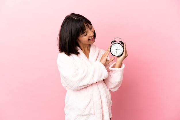Jovem mestiça grávida isolada em um fundo rosa, de pijama e segurando o relógio com uma expressão feliz