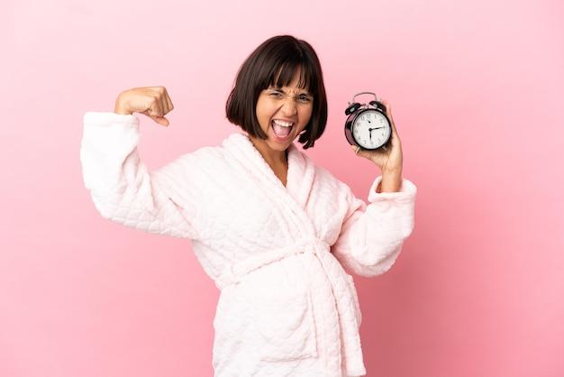 Jovem mestiça grávida isolada em um fundo rosa de pijama e segurando o relógio enquanto faz um gesto forte