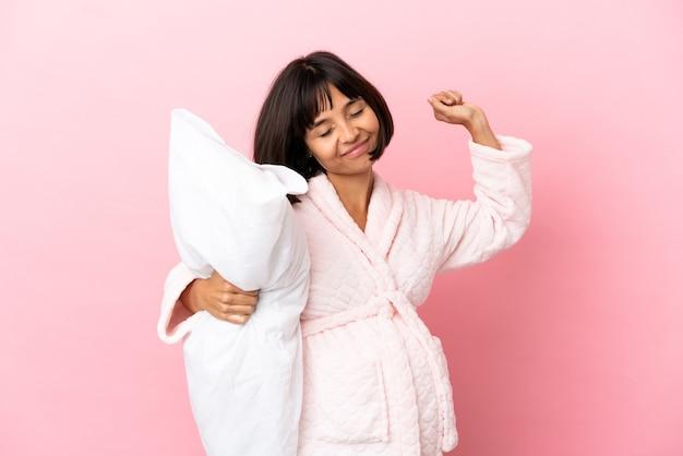 Jovem mestiça grávida isolada em um fundo rosa, de pijama, segurando um travesseiro e bocejando