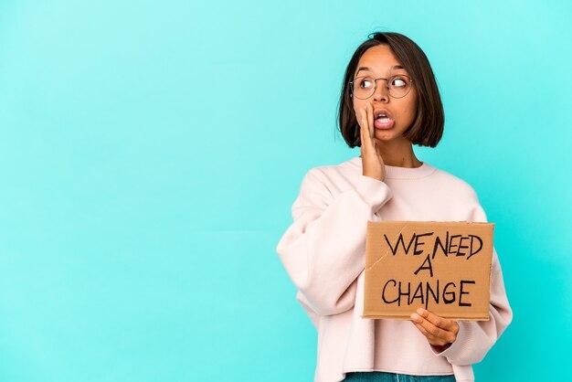 Jovem mestiça hispânica segurando uma mensagem inspiradora de mudança em papelão está contando uma notícia secreta de travagem e olhando para o lado