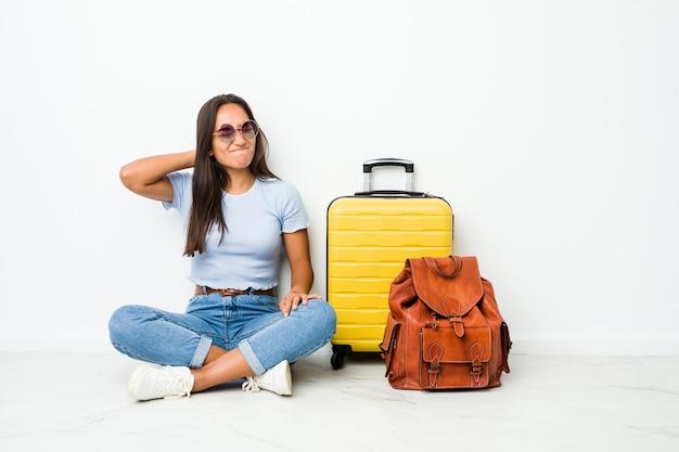 Jovem mestiça indiana pronta para viajar, sofrendo de dores no pescoço devido ao estilo de vida sedentário.