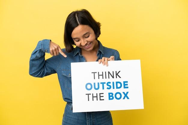 Jovem mestiça isolada em um fundo amarelo segurando um cartaz com o texto pense fora da caixa e apontando-o