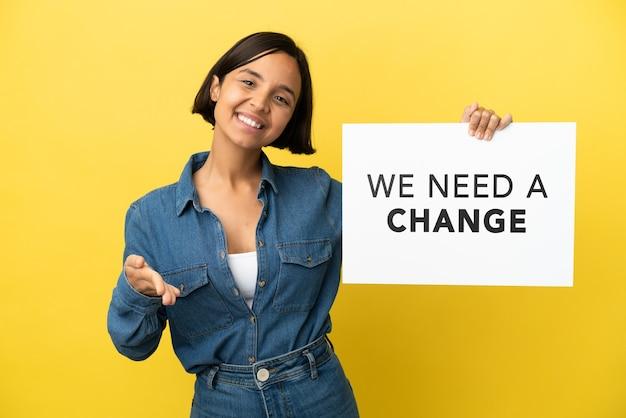 Jovem mestiça isolada em um fundo amarelo segurando um cartaz com o texto precisamos de uma mudança fechando um acordo