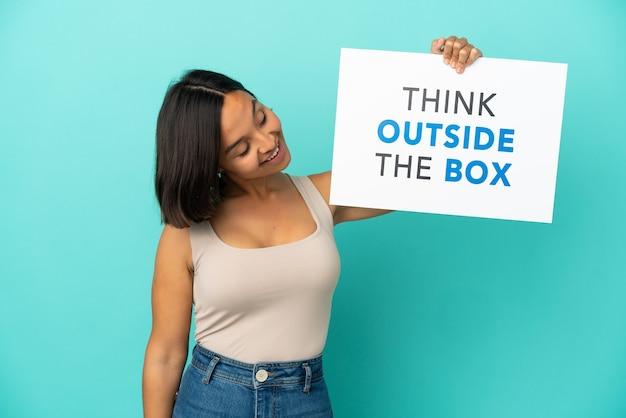 Jovem mestiça isolada em um fundo azul segurando um cartaz com o texto pense fora da caixa