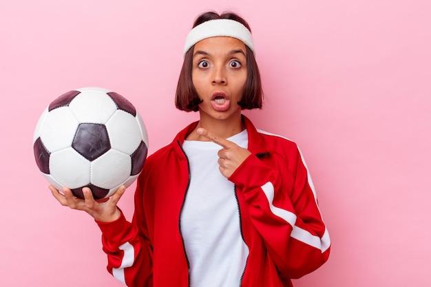 Jovem mestiça jogando futebol isolada em uma parede rosa apontando para o lado