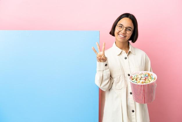 Jovem mestiça segurando pipocas com um grande banner sobre um fundo isolado feliz e contando três com os dedos