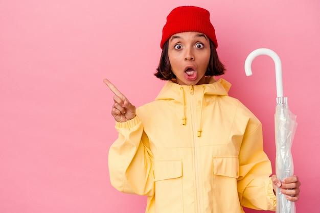 Jovem mestiça segurando um guarda-chuva isolado na parede rosa apontando para o lado