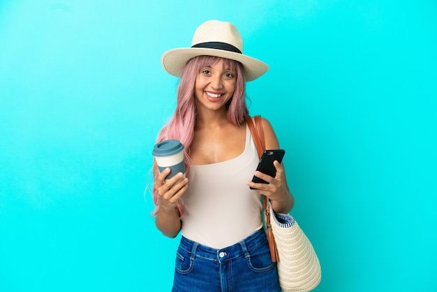 Jovem mestiça segurando uma bolsa de praia com pamela isolada em um fundo azul segurando um café para levar e um celular